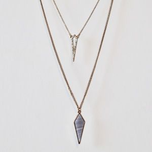 Gold necklace with a purple arrow pendant.